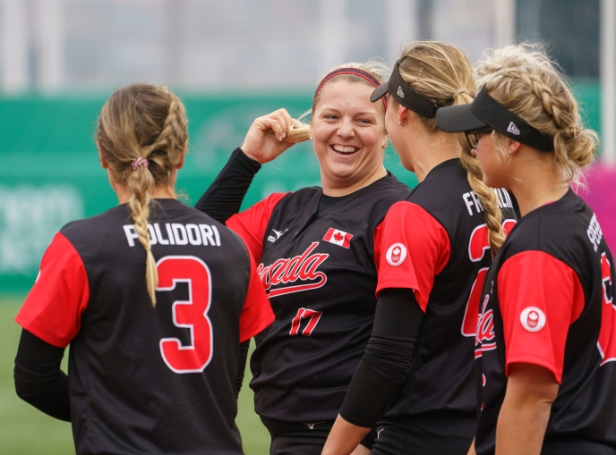 Members of women's softball team talking in a huddle