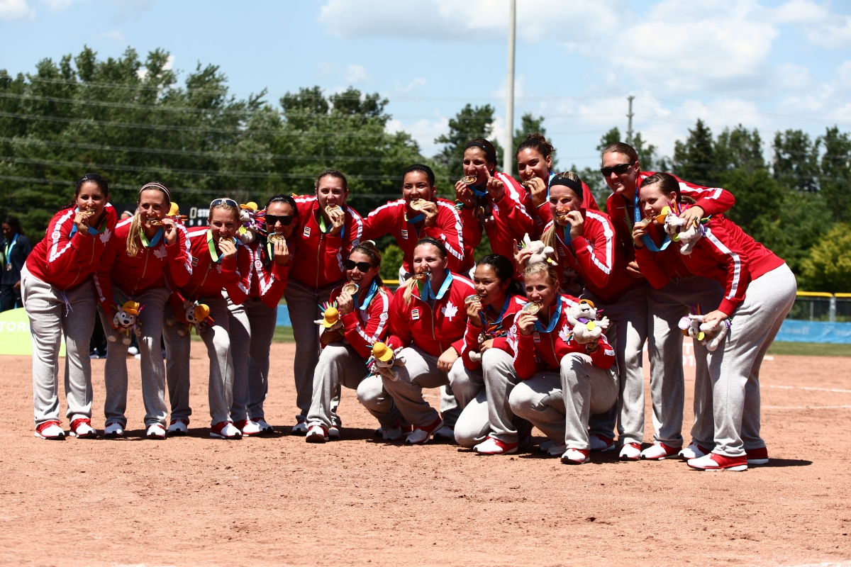 The womens softball team bites their medals