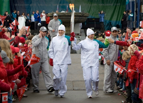 Two torchbearers run through a crowd holding the torch aloft