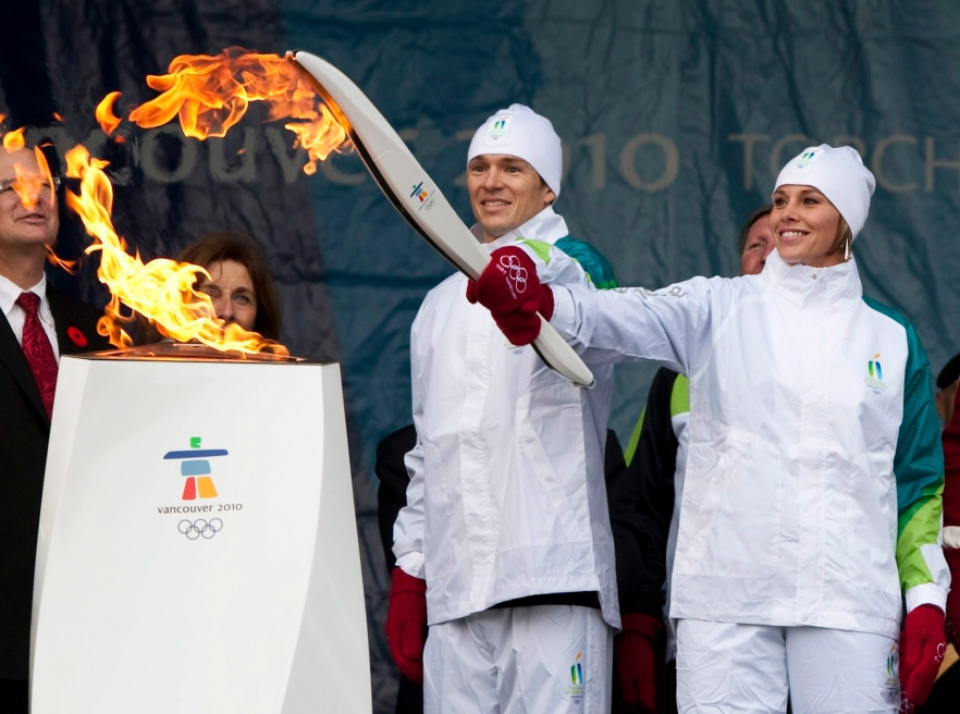 Two torchbearers light their torch from a cauldron