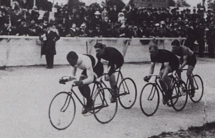"""Black and white image of Marshall """"Major"""" Taylor racing in Paris in 1908."""