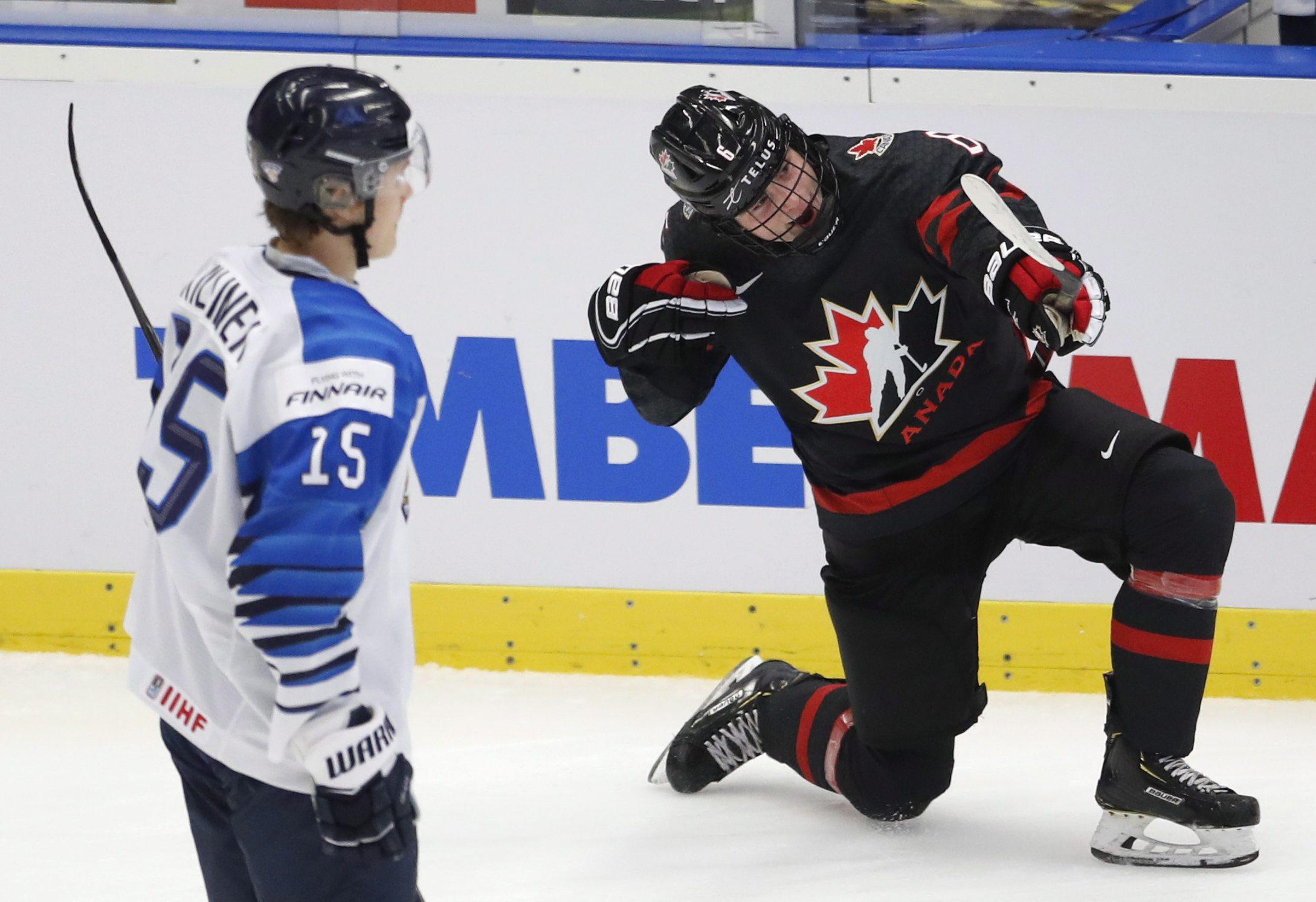 Un joueur du Canada célèbre un but devant un joueur de la Finlande.