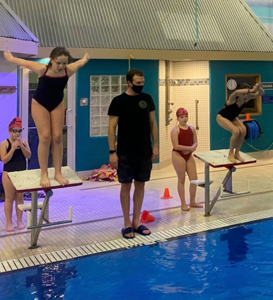 Coach with swimmers on start blocks