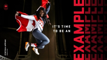 Bobsledder jumping with a Canadian flag
