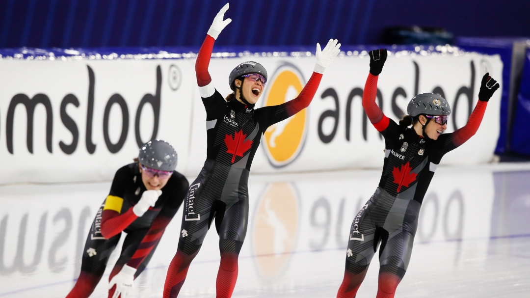 Valerie Maltais, center, Ivanie Blondin, right, and Isabelle Weidemann, left, celebrate setting a new track record and winning the women's team pursuit race.