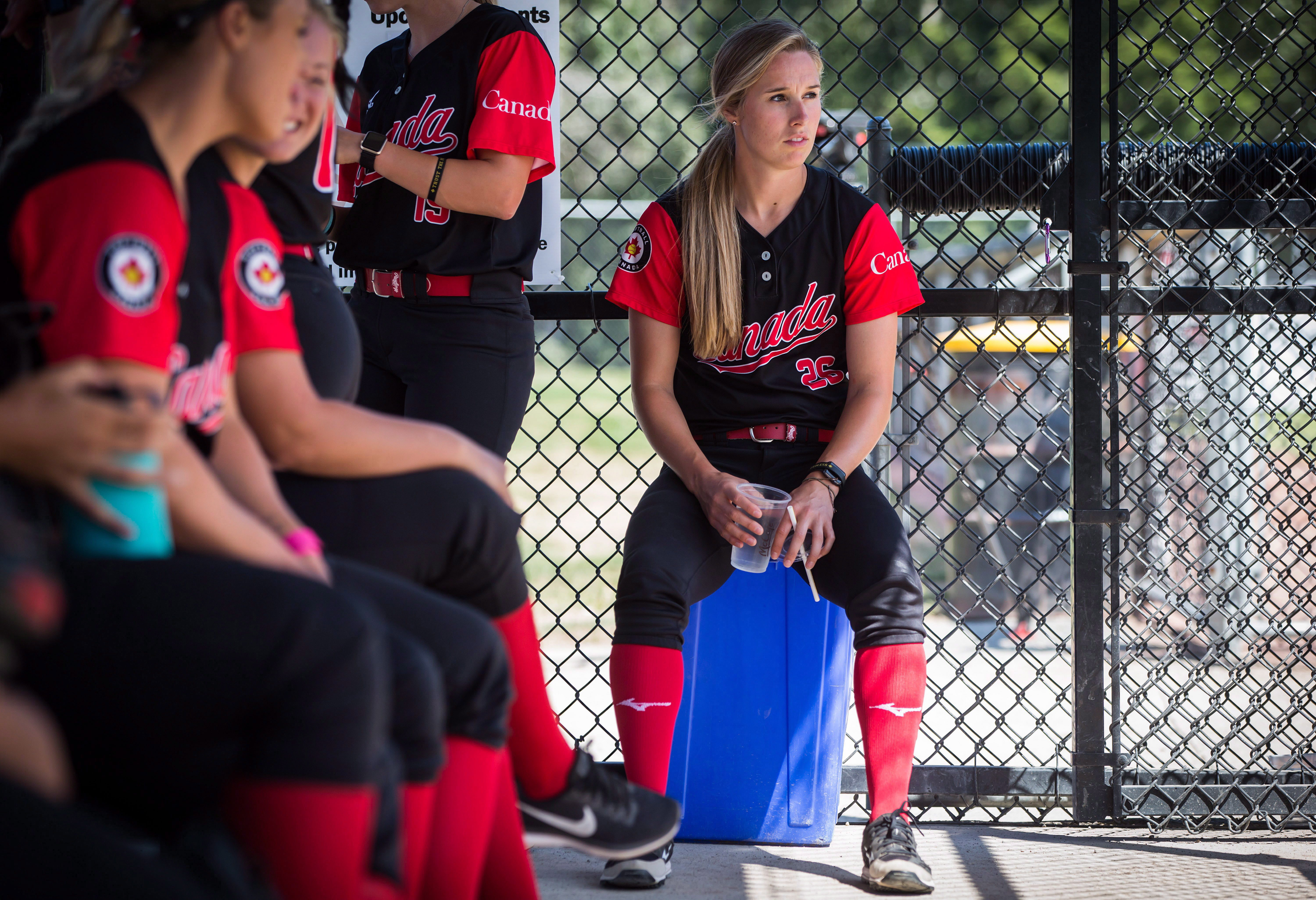 Softball player sits in dugout with teammates