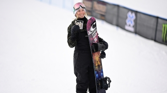 Laurie Blouin holds up her medal and hugs her snowboard at the X Games.