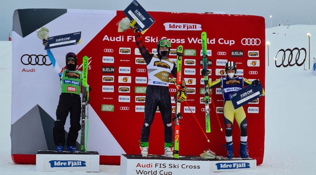 Reece Howden stands on the podium at the Ski Cross World Cup after winning gold