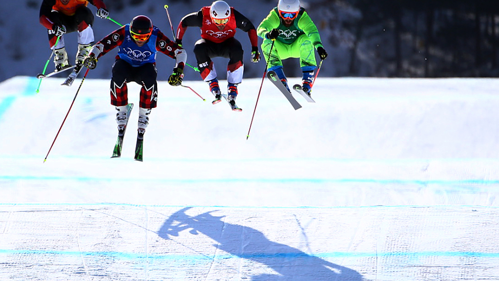 Four skiers up in the air while on a jump racing in ski cross at the PyeongChang 2018 Olympic Winter Games.