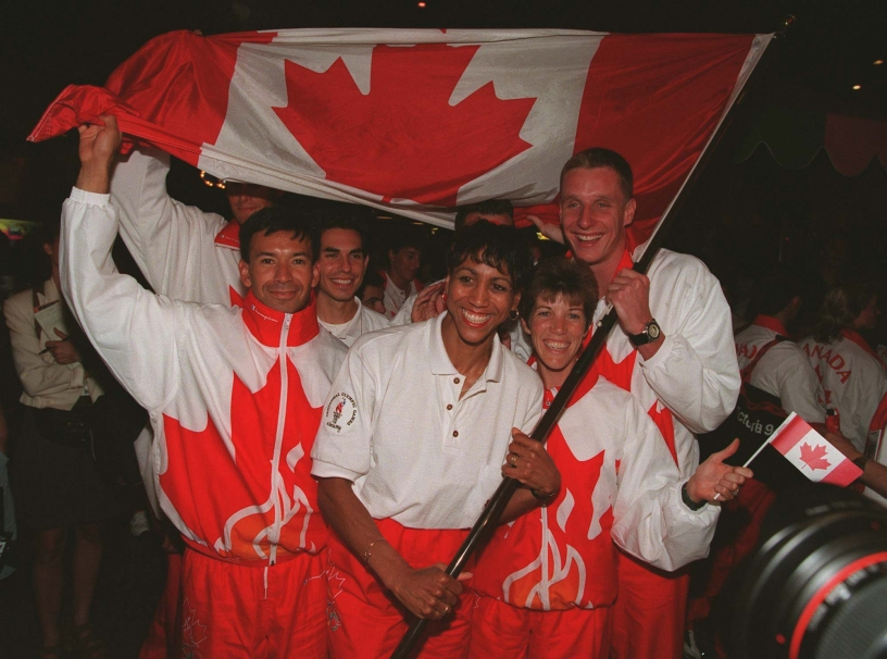 Charmaine Crooks of Vancouver, B.C. the flag bearer for Canada's Olympic team celebrates with teammates (left to right) Toronto race walker Janice McCaffery and Brampton, Ont. swimmer Stephen Clarke. (CP PHOTO) 1996 (stf-Andrew Vaughan)