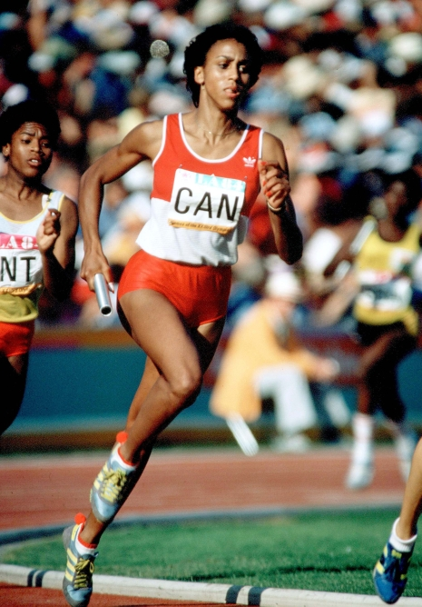 Charmaine Crooks running with a baton