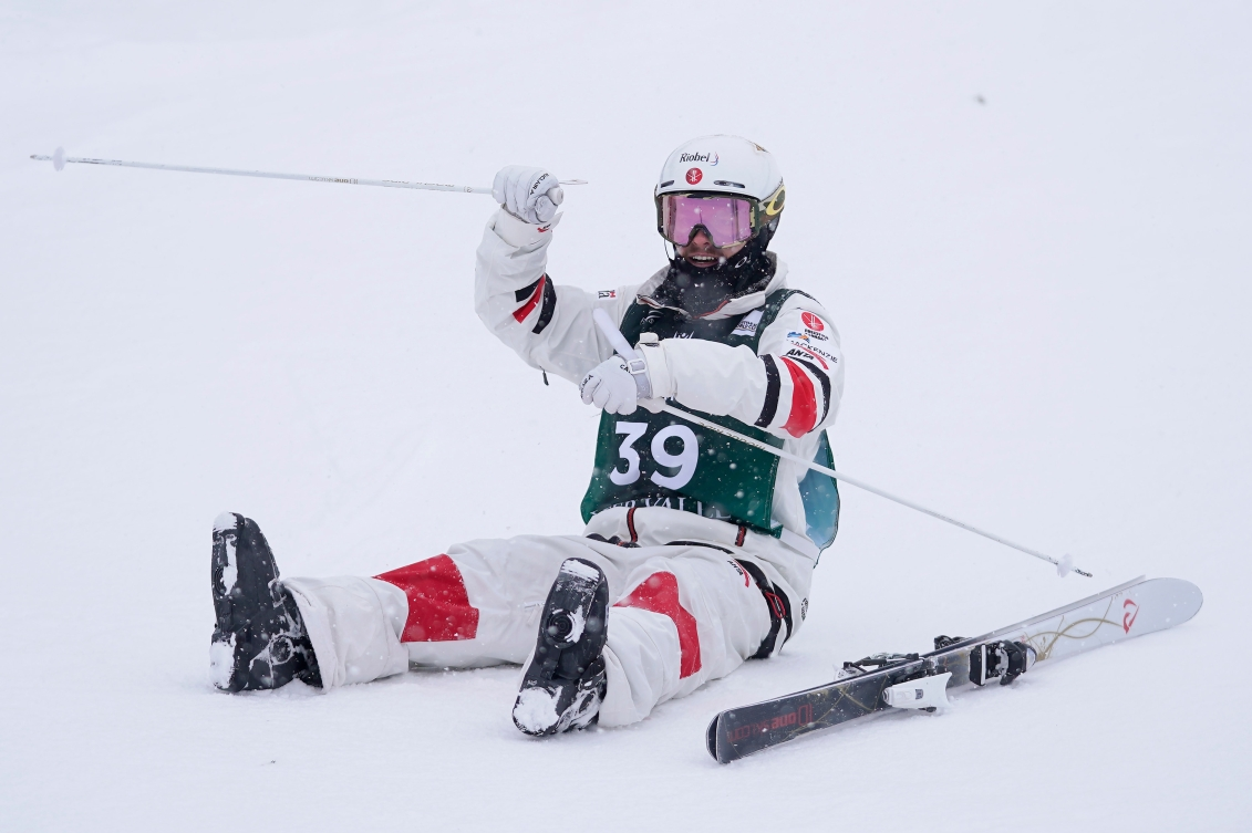 Mikaël Kingsbury sits on the ground after winning gold.