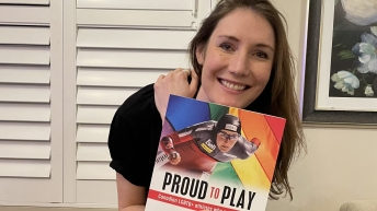 Woman holding a book with the title Proud to Play