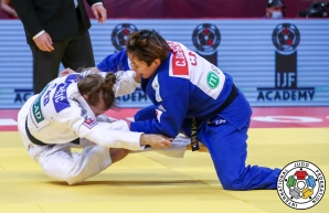 Christa Deguchi (in blue) takes down Serbia's Marica Perisic during a judo match.