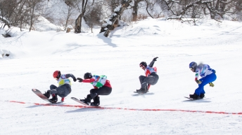 Four snowboard cross athletes reach the finish line.