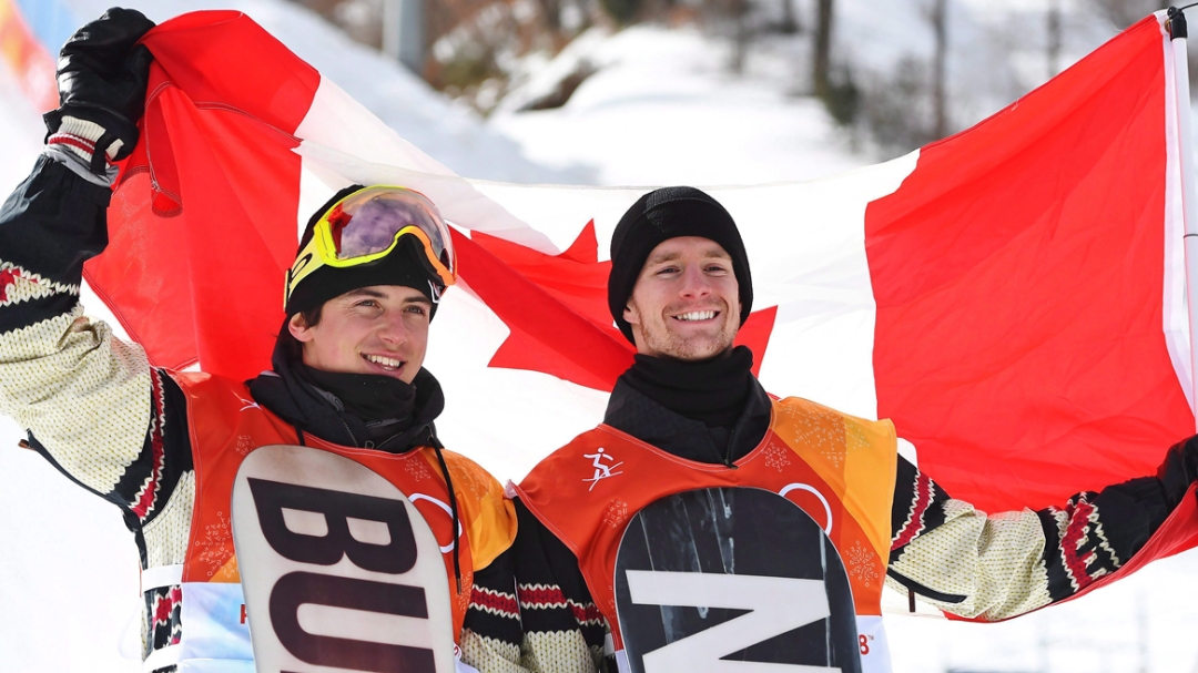Mark McMorris (lef) holds up the Canadian flag behind him with Max Parrot.