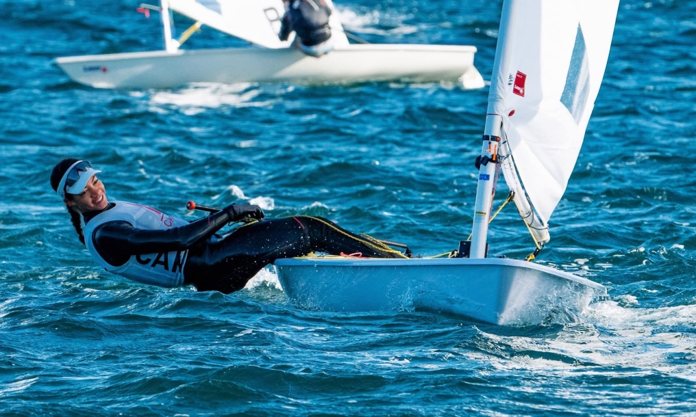 Sarah Douglas leans back over the water while sailing her boat
