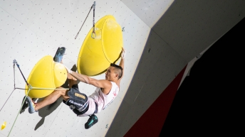 Sean McColl hangs off two handholds during a lead climbing event