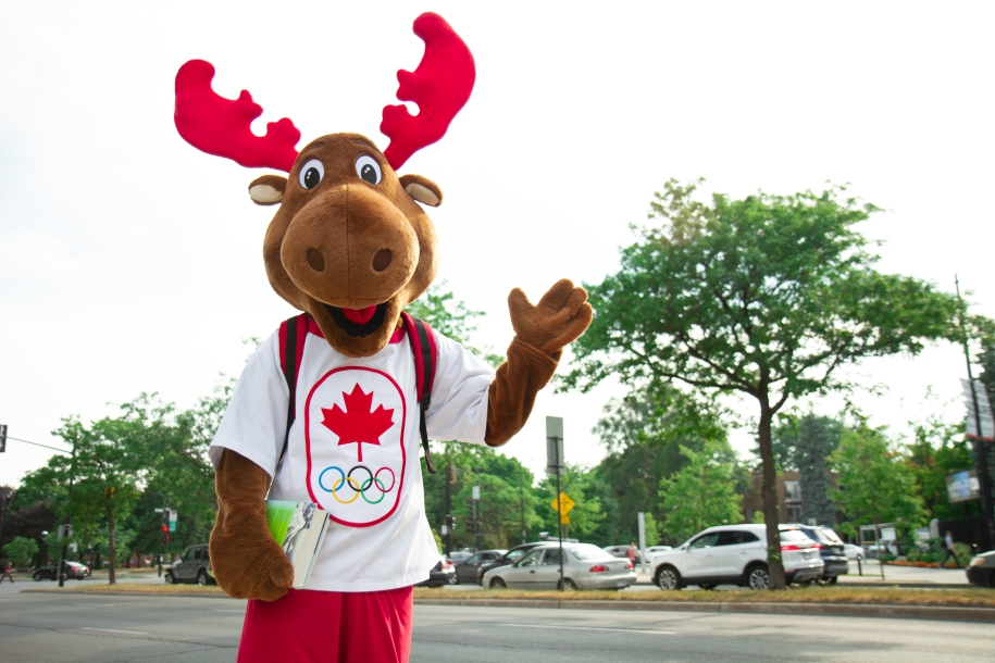Team Canada's mascot, Komak the moose, is waving with a backpack on