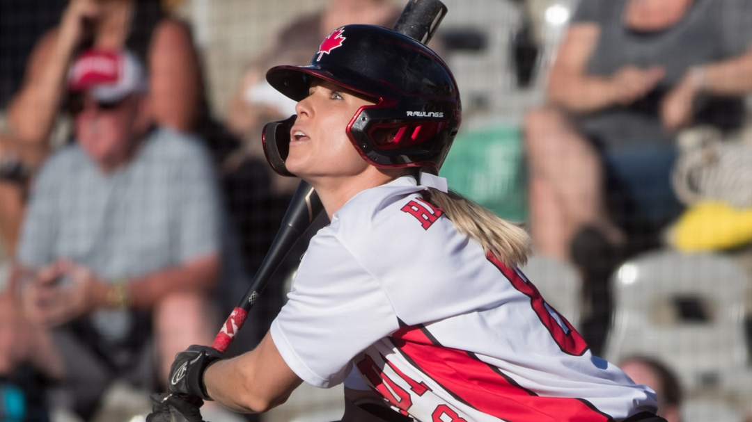 A softball player watches the ball after hitting it with the bat. An out of focus crowd behind her.