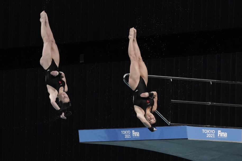 Canada's Meaghan Benefeito and Caeli McKay perform a dive during the women's synchronized 10-meter platform preliminaries at the FINA Diving World Cup Sunday, May 2, 2021, at the Tokyo Aquatics Centre in Tokyo. (AP Photo/Eugene Hoshiko)
