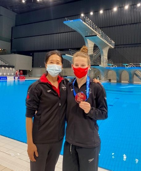 Diver and her coach pose with bronze medal