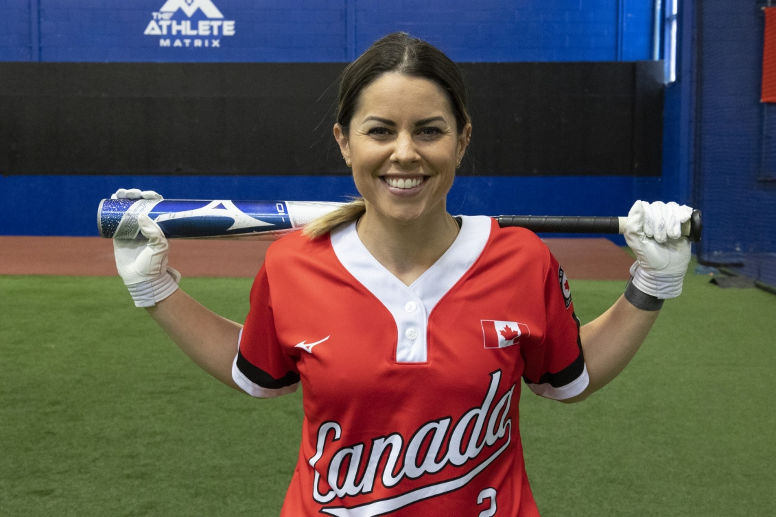 Natalie Wideman holds bat on shoulders while posing for camera