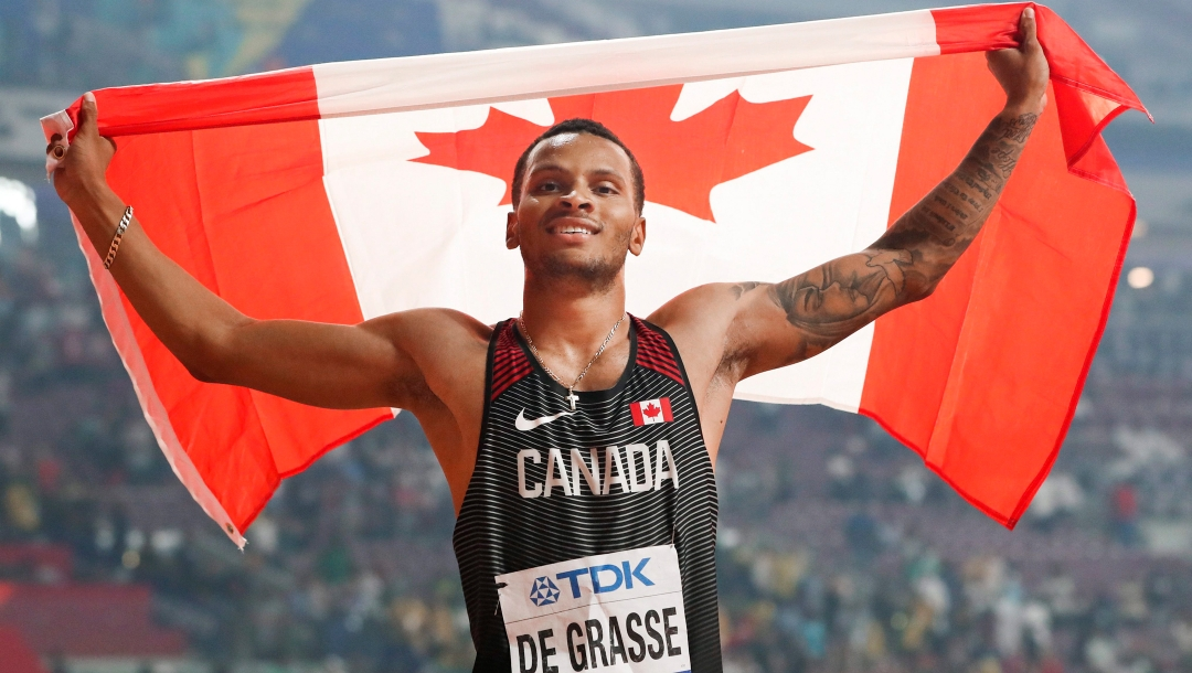 Andre De Grasse holds up the Canadian flag behind his head.