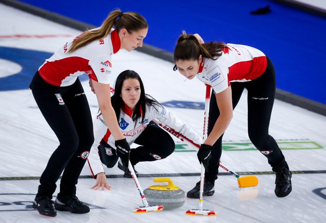 Kerri Einarson makes a shot as lead Briane Meilleur, left, and second Shannon Birchard sweep