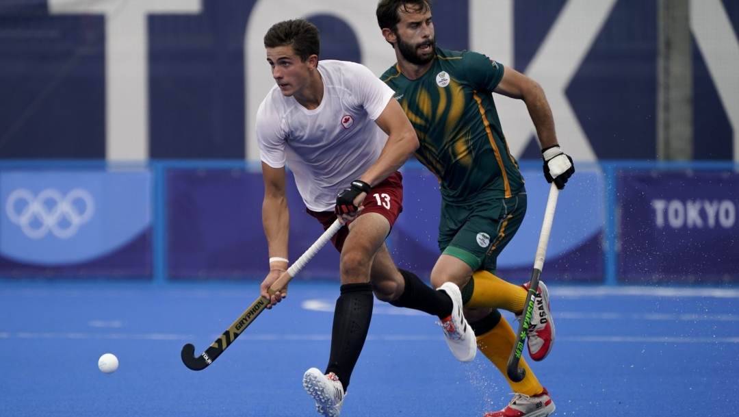 Field hockey player running with ball on his stick