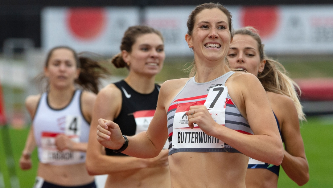A midshot of Lindsay Butterworth (front) smiling as she wins the 800m race. Behind her are three other runners.