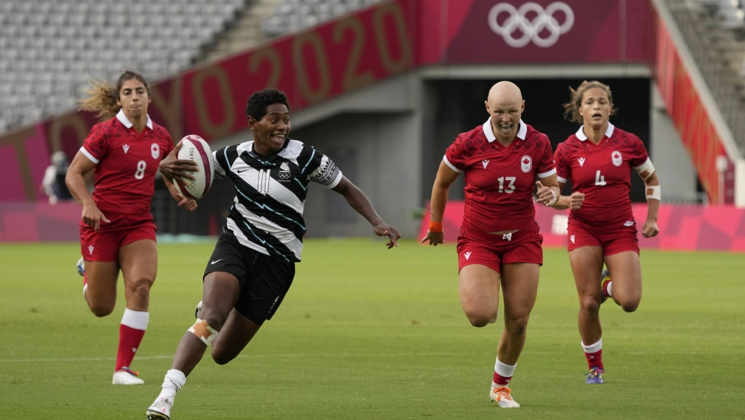 Canadian rugby players chase an opponent carrying a ball