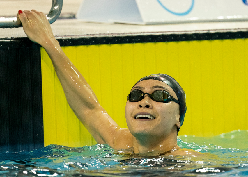 swimmer smiles in pool after winning race