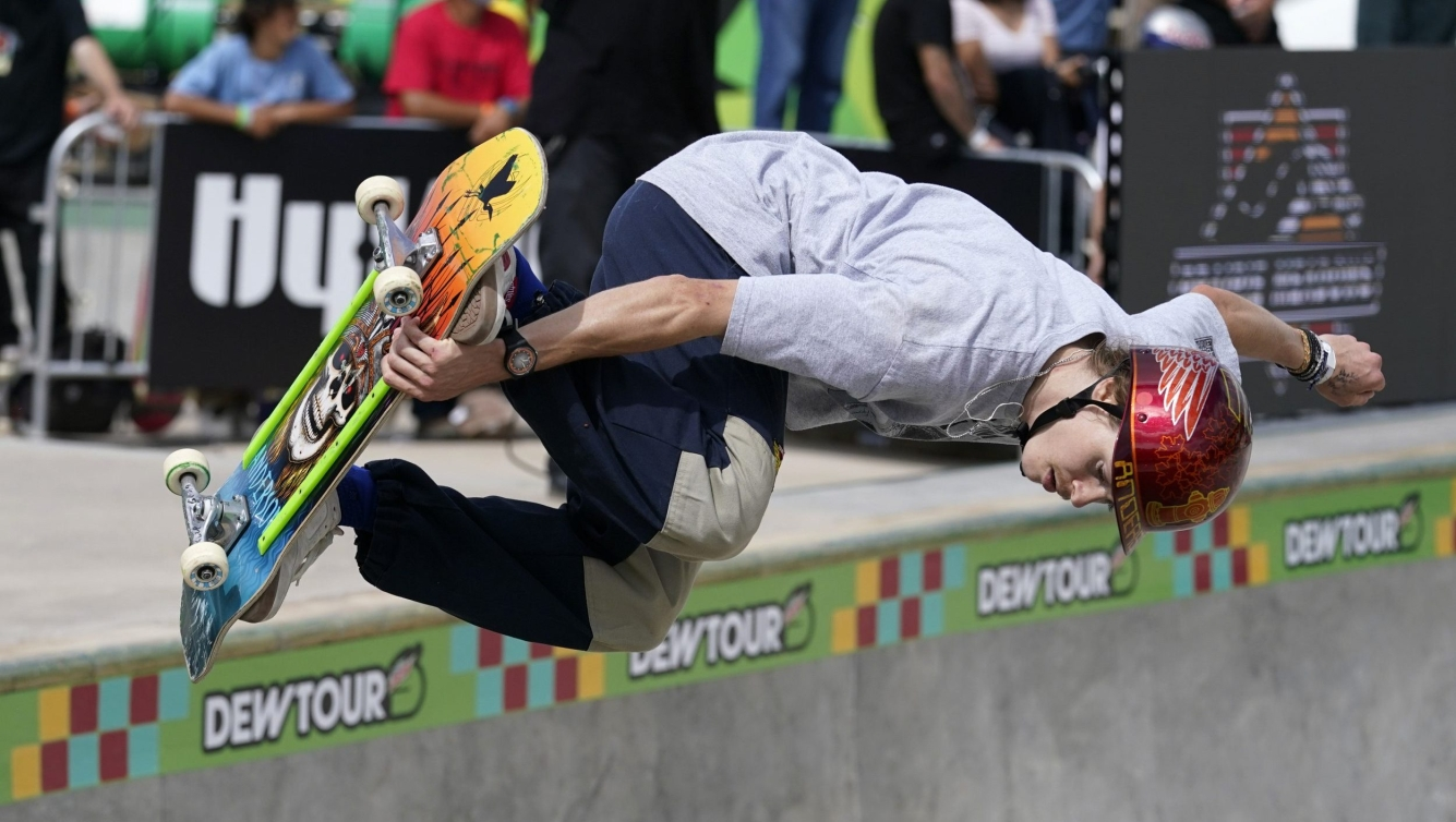 Andy Anderson grabs his skateboard on a trick