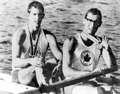 A black and white image of rowers George Hungerford and Roger Jackson sitting in their boat, holding their Olympic medals.