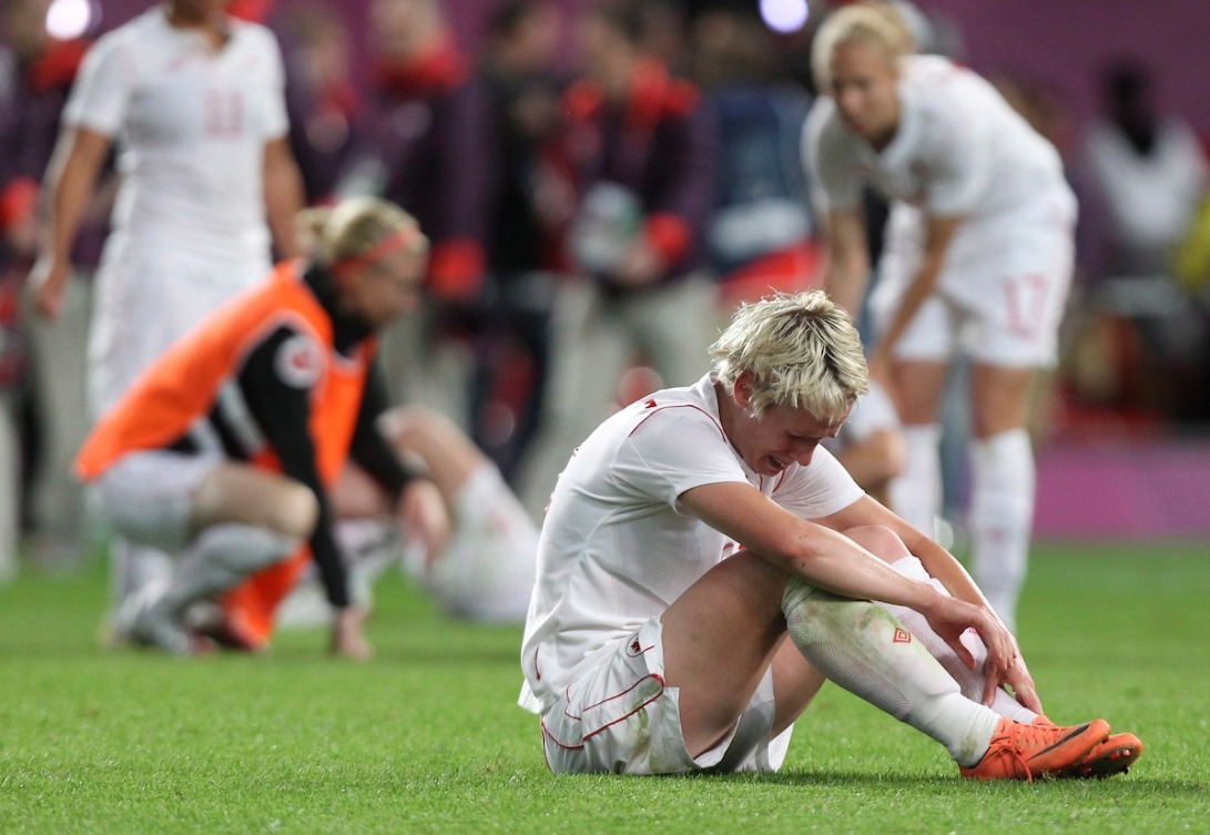 Sophie Schmidt sits on the field crying after Canada's loss to the USA at London 2012