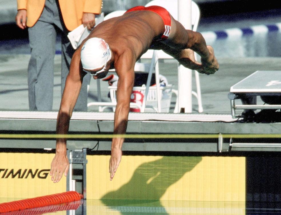 A photo of swimmer Alex Baumann, in a white swim cap, diving into the pool at the 1984 Olympics.