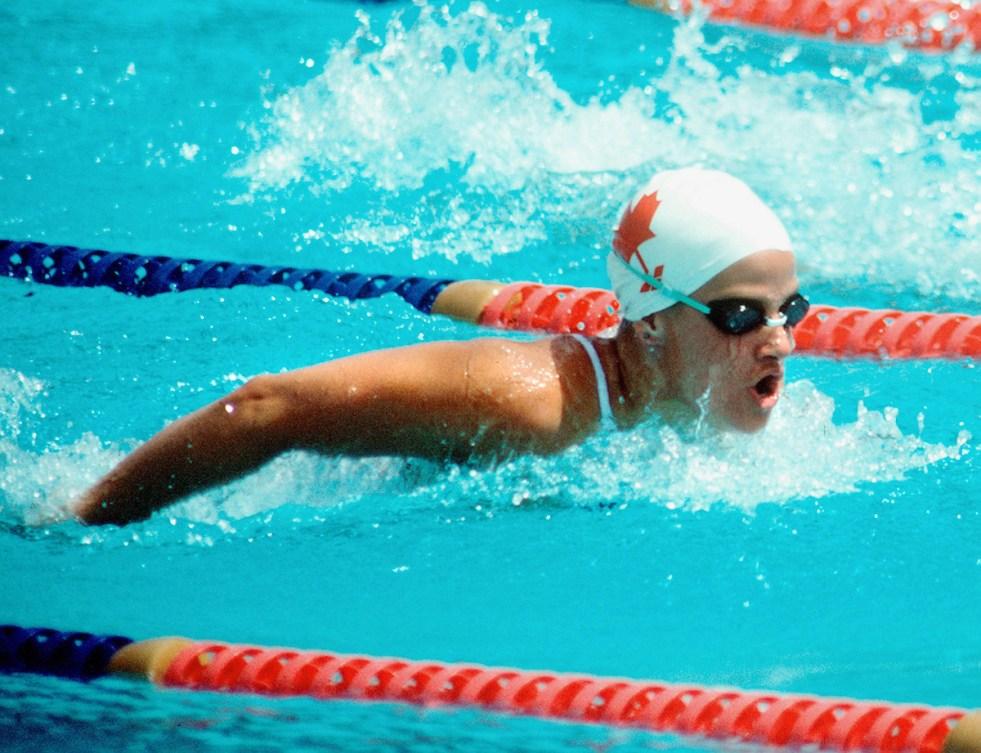 A photo of Nancy Garapick swimming in a red maple leaf swim cap between lane markers.