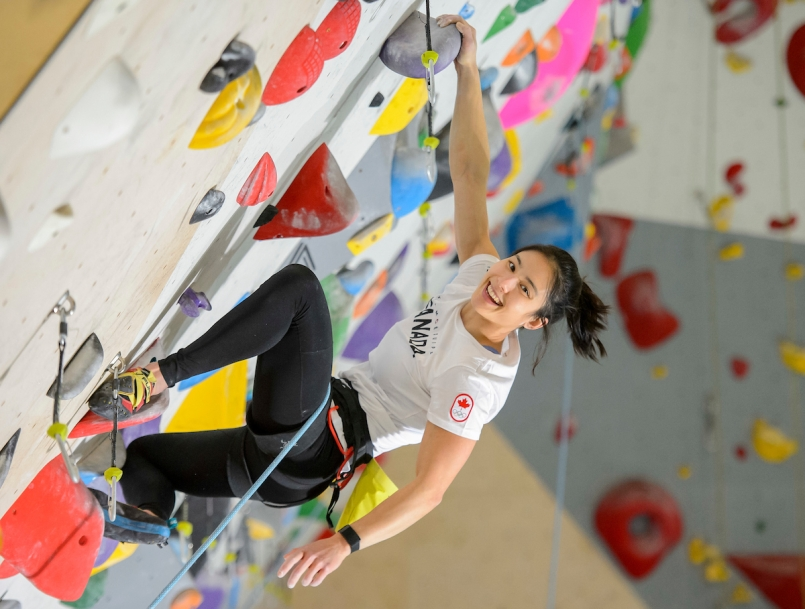 female athlete wearing a harness is climbing a rock wall smiling at the camera