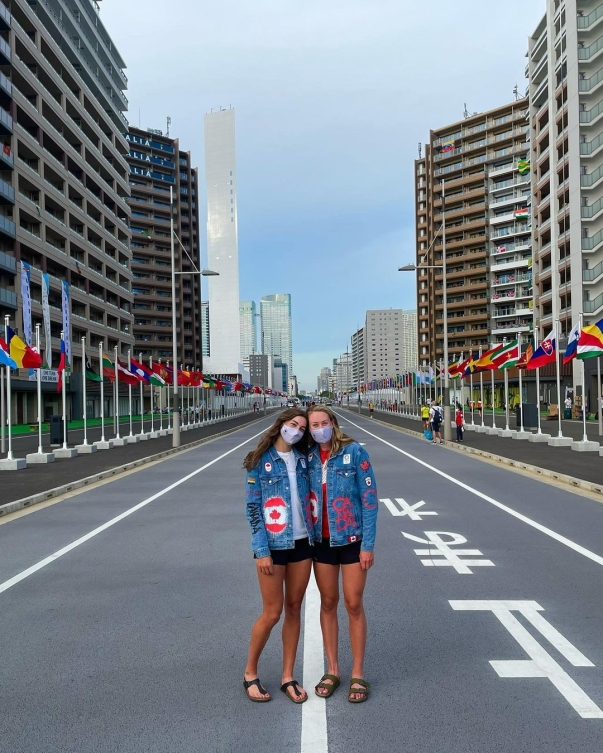 Two female athletes standing in the middle of flag street for a picture