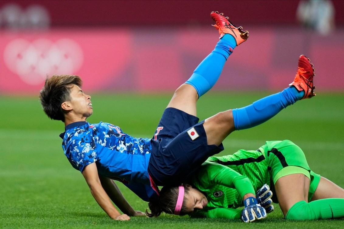 Japan's Mina Tanaka falls on top of Canadian goalkeeper Stephanie Labbe's head following a collision.