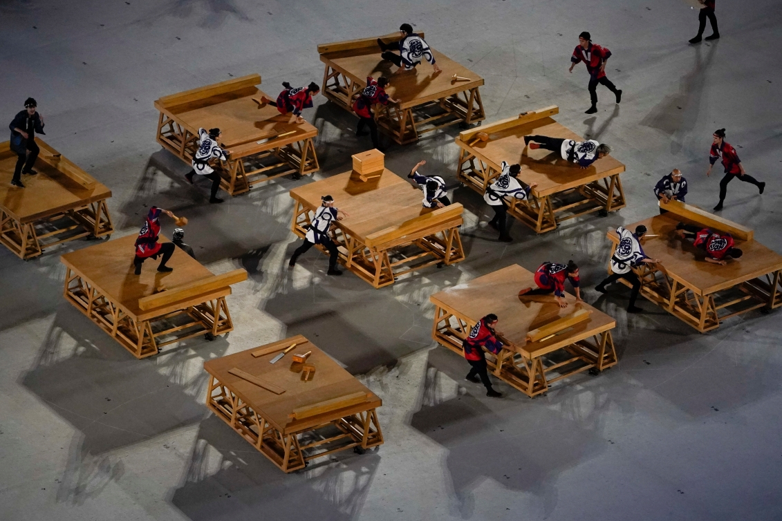 Dancers performing on tables with wooden props.