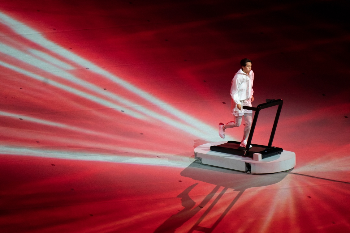 A performer is pictured on a treadmill with beams connecting them to the other performers.