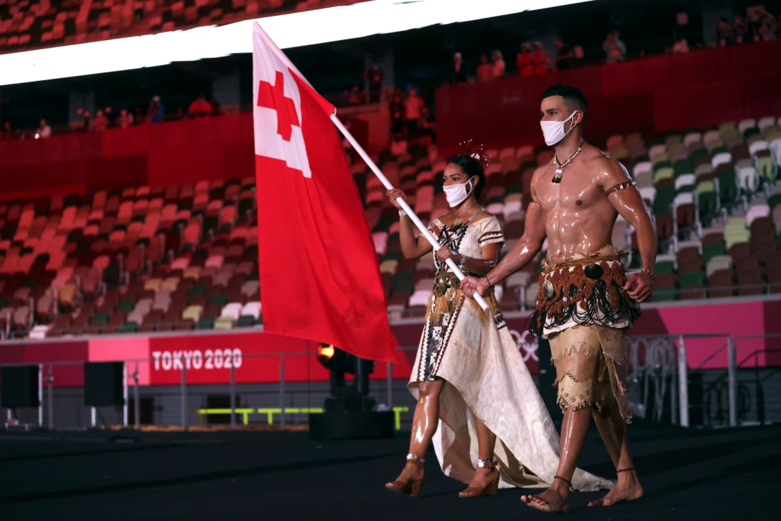 Malia Paseka and Pita Taufatofua carry the Tongan flag in to the Opening Ceremony.