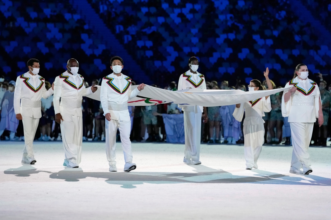 Six athletes carrying Olympic flag.