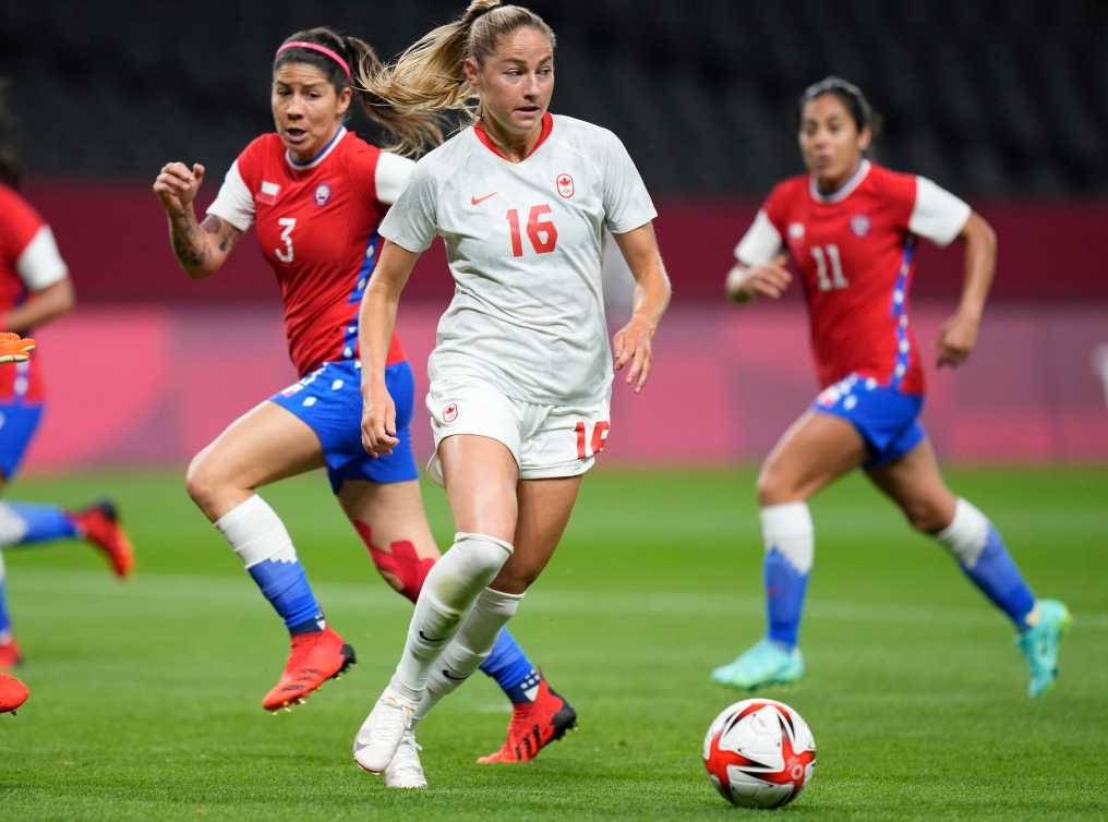 Canadian player Janine Beckie controls the ball at her feet, with two Chilean players in the background.