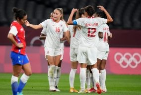 Four Canadian players in white, including Janine Beckie, stand in a circle on the field.