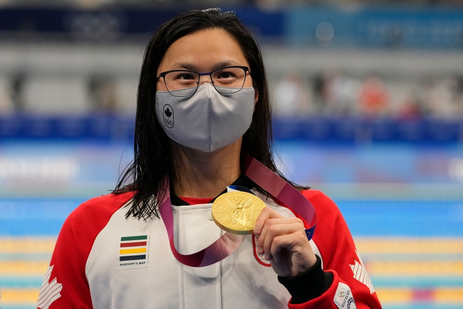 Swimmer Margaret Mac Neil, wearing a Canada jacket and protective mask, holds up her Olympic gold medal.
