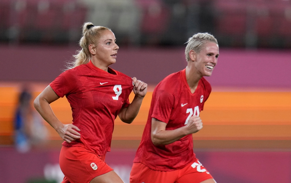 Soccer player Adriana Leon, alongside teammate Sophie Schmidt, holds up the Canada crest on her jersey.