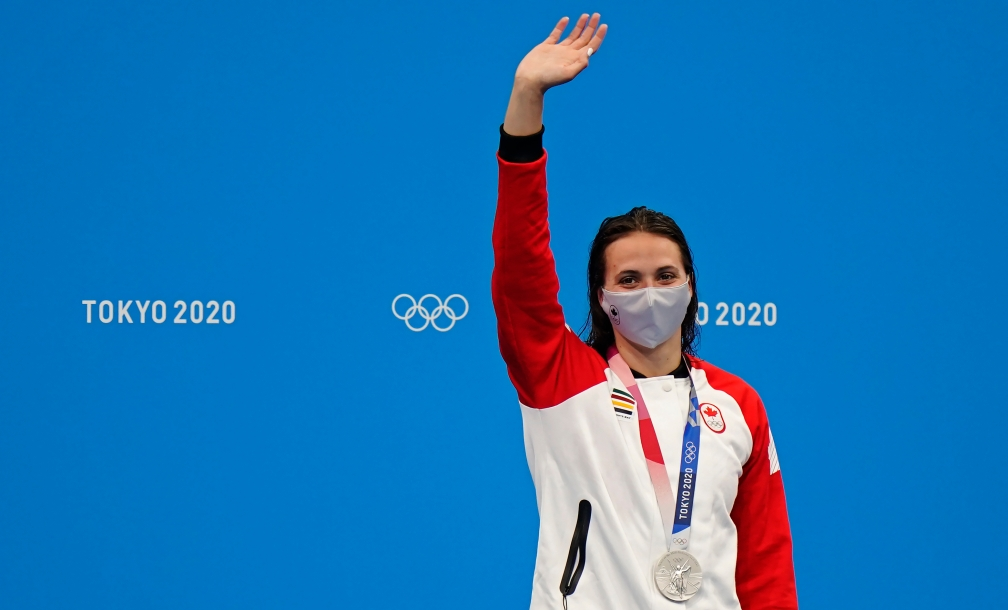 Kylie Masse in a Canada jacket, waving with her silver medal around her neck